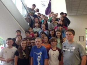 Students posing on steps of lobby during STEM visit to Roper